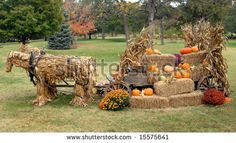 Autumn display has horses composed of corn husks.  They are pulling a loaded wagon of pumpkins, hay and cornstalks.