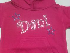 Dani hoodie, written in the fun,bubbly Curlz font with two little stars either side. Done in a mix of clear rhinestones and aqua blue rhinestuds on a hot pink hoodie.We can make this design in any colour for you and apply it to a huge variety of garments. For more info/pictures you can visit our website or give us a call!