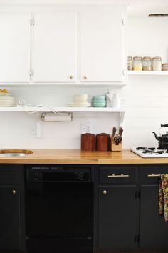 Outdated wood cabinets are re-painted with in a beautifulblack. The bold color choice creates contract between the all white uppercabinets and the cabinets underneath the butcher-block countertop in MandiJohnson of A Beautiful Mess' kitchen renovation.
