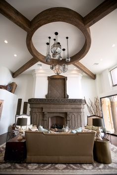 Cosa Belle Interiors: Custom wood beams with unique mirrors lighting, stained marble fireplace and custom furnishings.