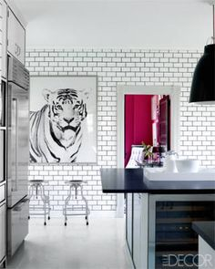 The kitchen's stools are by Design Within Reach, the ceiling fixture is from YLighting, the refrigerator and wine cooler are Sub-Zero, and the photograph is from Natural Curiosities.