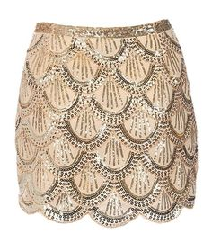 Flapper Riches Skirt: Features a double layer design with tonal liner for full coverage, all-over gold fishscale sequin pattern highlighting intricate scalloped lines throughout, and a hidden side zip closure to finish.