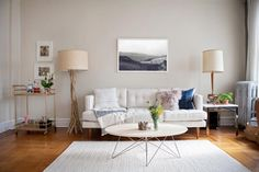 This contemporary living room features a white sofa, driftwood floor lamp and a copper bar cart.