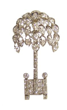 An Art Deco Diamond Brooch by Henri Picq in the form of an ornamental bay tree. The brooch set with a mixture of brilliant and square cut diamonds, set in platinum. Marks for Henri Picq and Platinum. French, Circa 1920. Picq was a supplier to Cartier.