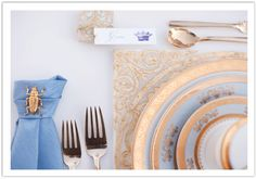 Luxury gold and periwinkle blue place setting on top of a gold and white tile as a charger by Alchemy Fine Events