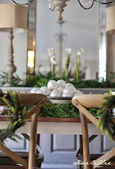 wreaths on backs of chairs and bowl filled with ornaments, wrapped with greenery | dear lillie blog