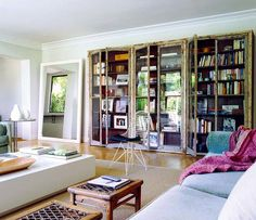 Eclectic, bohemian living room with amazing wall to wall, glass front bookcases!