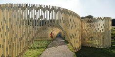 Trylletromler / Fabric Architecture Pabellón con una enorme estructura curvilínea y descubierta hecha de madera.