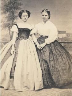 c.1861-1865, young ladies in day wear skirts and blouses, 1 with a Swiss body & long sash.