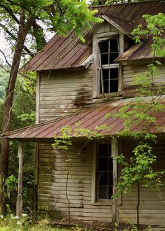 The windows and rusted tin roof of this old abandoned house tell a story from the past. Once a place of life, the weathered boards still stand, hanging on to the memories of yesterday.
