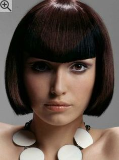 Dark brown bob hairstyle with a slightly angled cutting line. Modern bangs with a dip in the middle.