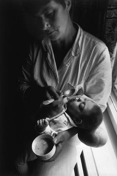 RUSSIA. CHERNOBYL/BELARUS. 2000. Nurse, Alla Kamarova, at the Childrens Home No. 1. Minsk, Belarus is feeding an infant whose brain is contasined in a membraine growing from the back of his skull. Paul Fusco/Magnum Photos
