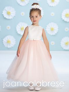 Sleeveless satin and tulle tea-length A-line dress with vertically hand-beaded jewel neckline, set in satin waistband with center bow, full gathered tulle overlay skirt. Sizes:  2 – 14 Colors: Ivory/Blush, Ivory/Petal, White