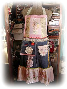 An apron made from many different pieces of needlework and part of a pair of jeans.  So darn cute !