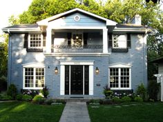 The blue-gray color lends a little fresh twist to this typical colonial architecture. Like all colonial styles, Georgian focuses on strict symmetry. It is typically a box shape and adorned with shuttered windows.  The style also features a paneled front door below a decorative crown, which is usually framed by simple, sometimes flattened, columns.
