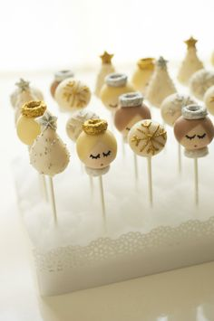 Darcy collaborated with NY Cakepops for these sweet angel pops — she sent an image of her paper angels to inspire their creation. For displaying cake pops, Darcy suggests using styrofoam edged with a strip of white paper that can be punched with a