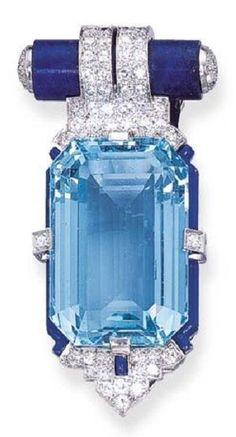 CARTIER AN ART DECO AQUAMARINE, DIAMOND, LAPIS LAZULI AND ENAMEL CLIP, BY CARTIER. Set with a rectangular-cut aquamarine, held by single-cut diamonds, within a blue enamel frame enhanced by a diamond-set and enamel palmette terminal, to the lapis lazuli tubular top with single-cut diamond detail, circa 1925. Signed Cartier, numbered. #Cartier #ArtDeco #clip