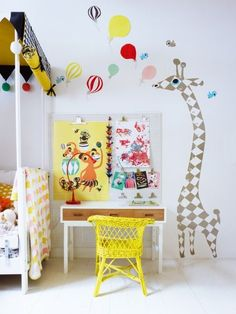 yellow chair and colorful desk corner for a childs room, lovely giraffe wall picture too
