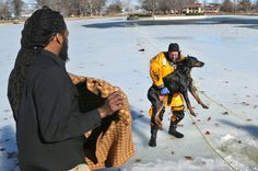 Description of . Jason Newsome, left, waits near the shore to wrap his dog, Diablo, as St. Louis firefighter Stan Baynes carries him from th...