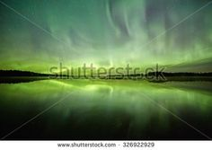 Stock Photo: Northern lights (Aurora Borealis) above a lake with still water and reflections at night. Stars on the night sky behind the polar lights.