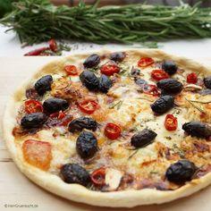 Pizza mit Peperoni, Schafskäse und schwarzen Kalamon-Oliven