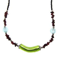 This handmade necklace features green glass arched tube center piece with garnet, glass and metal beads. Let this gorgeous piece of jewelry become the next treasured piece of your collection. Product