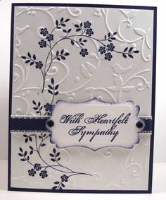 By NanaDiana at Splitcoaststampers. Uses stamp from Stampin Up Thoughts and Prayers stamp set. First, stamp the flowers. Then dry-emboss white cardstock panel with Cuttlebug Birds and Swirls embossing folder. Add ribbon and sentiment. (Her sentiment was inked on a die-cut with sponged edges.) Attach to card base.