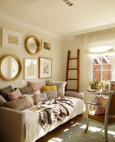 sofa cama con cojines, espejos, escritorio y escalera