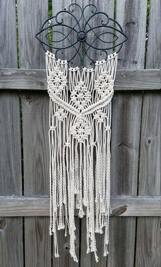 Medium sized macrame features a medallion on metal wall hanging. Overall size is 46 long, metal top is 15.75 x 10.75. This would make a wonderful housewarming, birthday, anniversary or wedding gift. The base color of the decorative metal piece is black but has subtle accents of turquoise and bronze.