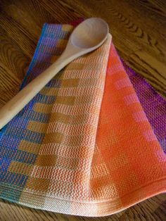 Gourmet kitchen towel hand woven and created with a bright rainbow of colors in the warp (length wise threads) and a lovely orange in the weft (horizontal threads) using a traditional twill weaving pattern in 100 percent cotlin yarn. Cotlin yarn has been spun with 60 percent linen