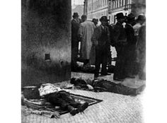 Bodies of dead paratroopers are lying on pavement for the identification. From front - Jan Hrubý, Jaroslav Švarc, Jozef Gabcík (it appears to me), Josef Valčík and Adolf Opálka (both hardly visible because of crowd).
