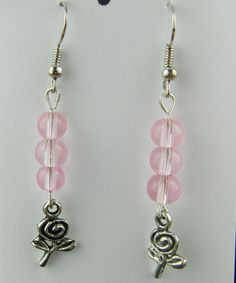 Earrings, Jewellery, Stud Earring, Accessories, Pink Round Bead, Gift, Birthday, Christmas, Beaded Jewellery, Silver Plated Rose Charm    These pretty earrings will put the finishing touches to any outfit you choose to wear everyday or for a casual evening out. They would make the perfect gift for a friend or relative, or a treat for yourself.    The earrings are made using a pink glass round beads with a silver plated rose charm, hung on silver plated ear wires and they have a drop of 4 cm…