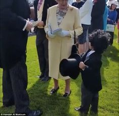 The monarch, wearing a flowery dress, yellow coat and sunhat, was talking with Dubai's ruler, Sheikh Mohammed bin Rashid al-Maktoum, when the boy approached, took off his hat and outstretched his hand