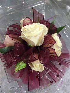Wristlet corsage with white spray roses, burgundy sheer ribbon, burgundy mesh and burgundy rhinestones.