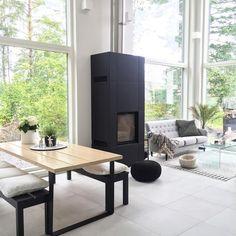 Rento retkimäinen pöytä, tumma takka ja huikean isot ikkunat luovat olohuoneen viihtyisän tunnelman.