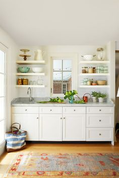 Instead of a traditional hutch design, the butler's pantry (located just off the kitchen) repeats the floating shelves. Outfitted with a sink, it's the perfect spot for flower arranging or to prep for baking.