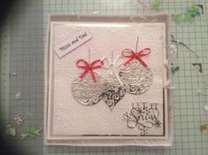 I matted and layered Silver Miri card with White card, then embossed the top white piece of card.  I then die cut 3 baubles and attached them to my card