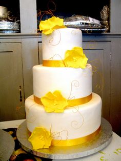 3-tier Wicked Chocolate wedding cake covered in white fondant decorated with yellow fondant floppy roses & yellow satin ribbon by Charly's B...