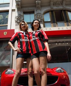 AC Milan girls posing in red-black jerseys in front of the red turbo powered Ferrari behind.