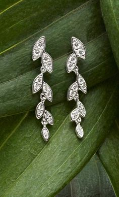 Brilliant pavé-set diamonds are framed in individually hinged leaf shapes to give these earrings a delicate, graceful movement.