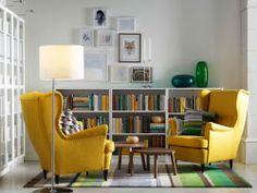 """Ein helles Wohnzimmer mit STRANDMON Ohrensessel und STRANDMON Hocker mit Bezug """"Skiftebo"""" in Gelb, weißen Regalen und Satztischen in Nussbaumfurnier"""