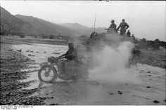 A German Panzer IV and a motorcycle rider crossing a small water stream . North Africa. Tunisia.1943