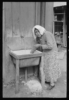 Old Mexican woman drawing water at community hydrant, San Antonio, Texas. 1939 Mar. Library of Congress.