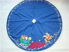 """This wonderful blue """"Merry Christmas"""" Tree Skirt is made of felt applique on cloth and decorated with hand~sewn sequins and beads. Santa's sleigh full of toys is being pulled by two of his reindeer with """"MERRY CHRISTMAS"""" appliqued in red in the center. White filigree sequins, stars and holly decorate the border with white snow sequins throughout and silver rick rack around the edge. Portions of this tree skirt are stuffed creating a 3-Dimensional appearance."""