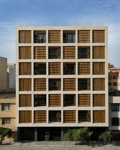 dezeen: Wavy wooden shutters cover gridded apartment block in Iran »