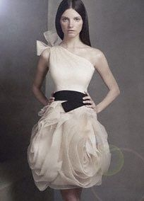 One-shoulder organza dress with hand-cut bias-flange skirt and elastic black belt.   Elegant, one shoulder gown with bias-cut flange skirt, and a waist-slimming elastic belt.  Raw-edged shoulder tie and flange skirt are signature Vera Wang details.  This is the kind of dress that inspires special occasions and celebrations, so we are also offering it in Ivory, making it an ideal reception dress for the bride.  Invisible side zip. Fully lined. Dry clean only.  Available in select stores in Ame...