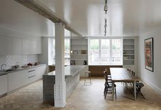 Love this renovated industrial space for its beams, floor, book shelves and light.