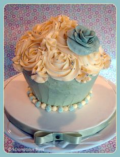 Pistachio & Ivory giant cupcake for the top tier of a wedding tower, tiny roses at the base and a large rose on top of buttercream swirls...    www.scrumptiousbuns.co.uk