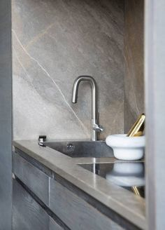 DISCREET: The sink is recessed into the cabinet wall.  Countertops and walls inside the niche is sandstone from Fired Earth.  Styling: Tone hook.