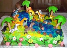 Homemade Jungle Birthday Cake: First I made some leaves and flowers from fondant. I also purchased a bag of animals. I baked a chocolate sheet cake. Then I covered it with yellow and